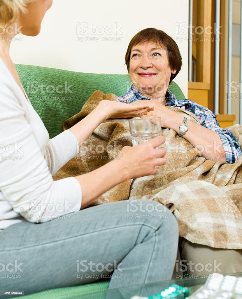 aged woman offering medicine and water to pensioner stock photo