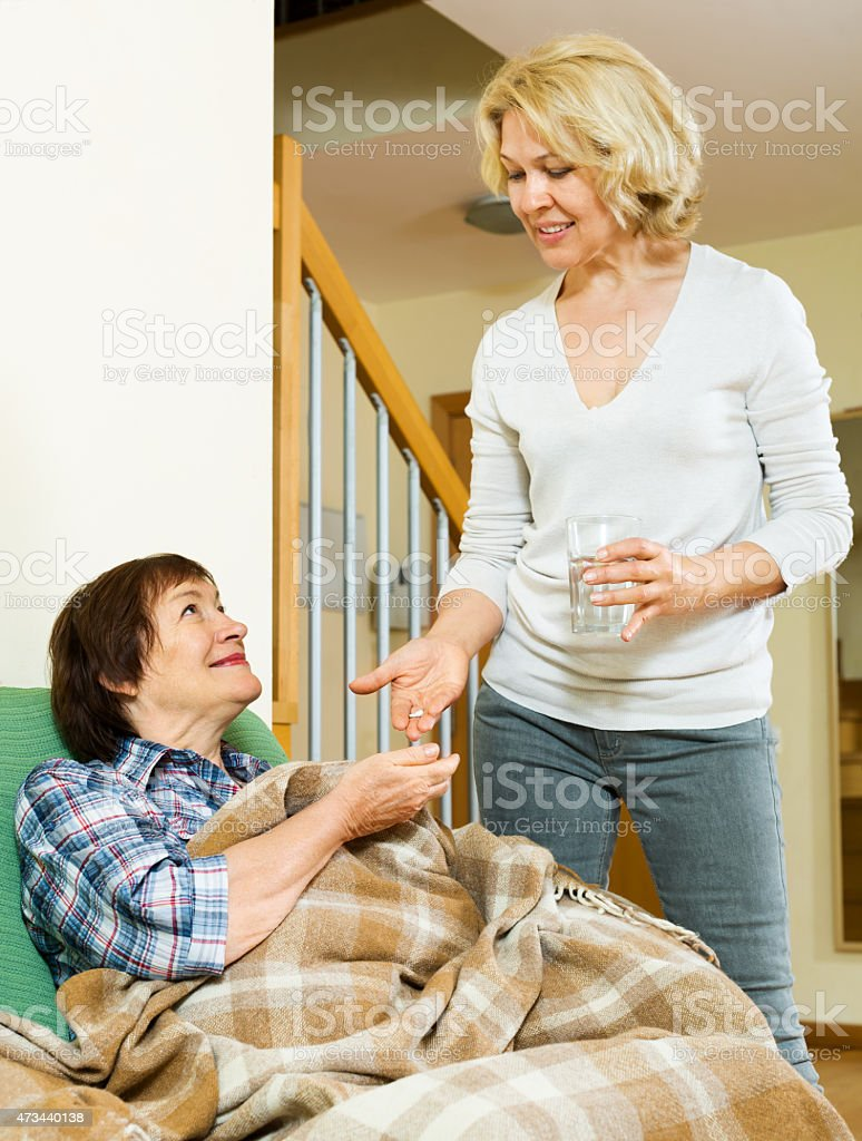 aged woman offering pills and water to pensioner stock photo