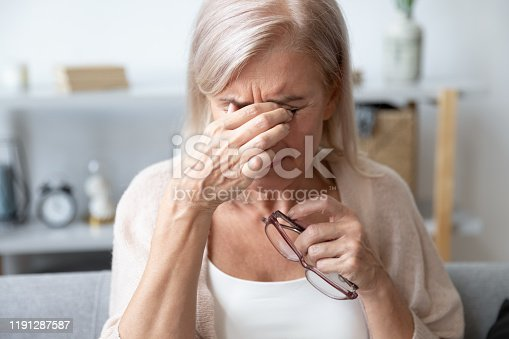 1049512672 istock photo Aged woman taking off glasses rubbing eyelid suffers from eyestrain 1191287587