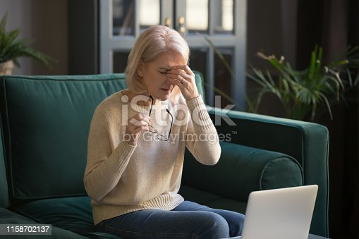 1049512672 istock photo Aged woman taking off glasses suffering from dry eyes 1158702137