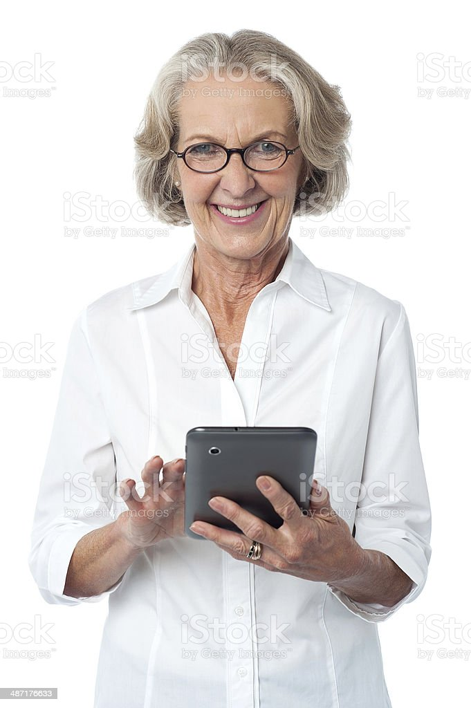 Aged woman using touch pad device royalty-free stock photo