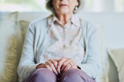 Cropped shot of a senior woman sitting on the sofa alone while in the living room of a nursing home