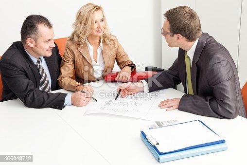 istock Agent Advises Couple Over Blueprint 466848712