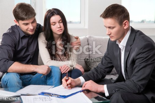 466848706 istock photo Agent advises the couple, signing documents 187429928