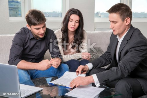 istock Agent advises the couple, signing documents 187441522