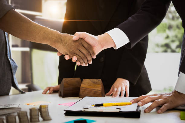 agent and customer meeting and handshaking after good deal for buy house. agreement and real estate concept. - real estate law stock photos and pictures