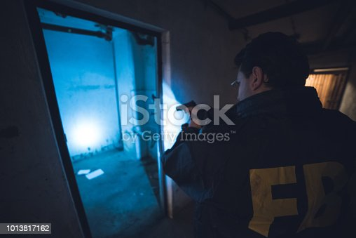 FBI agent holding a gun and investigating spooky surroundings