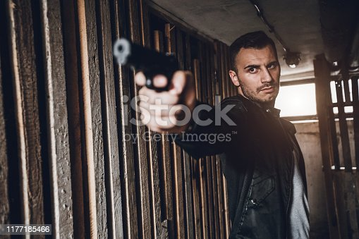 Young Caucasian male FBI agent with a gun on a mission.