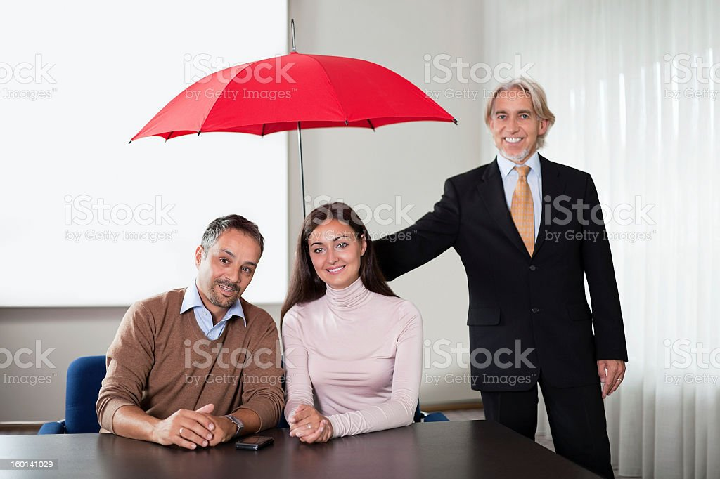 Agent providing insurance cover to a young couple stock photo