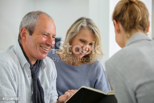 845085240 istock photo agent selling life insurance to retired couple 870198792