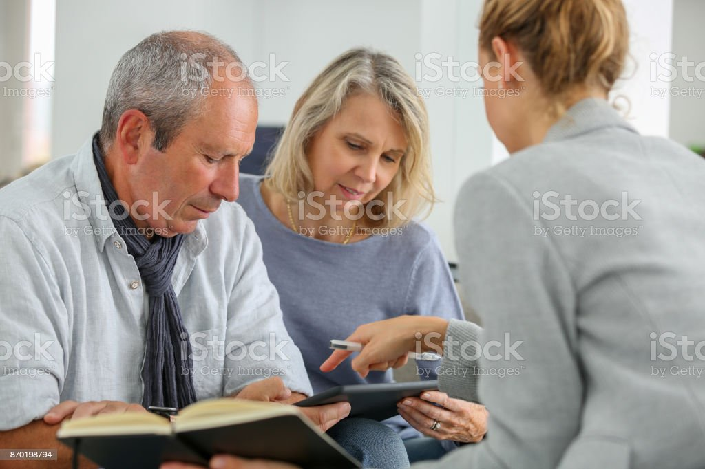 agent selling life insurance to retired couple stock photo
