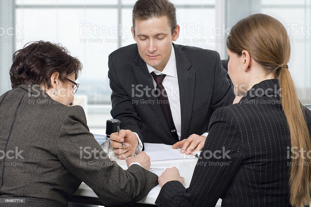 Agent signing documents with couple women stock photo