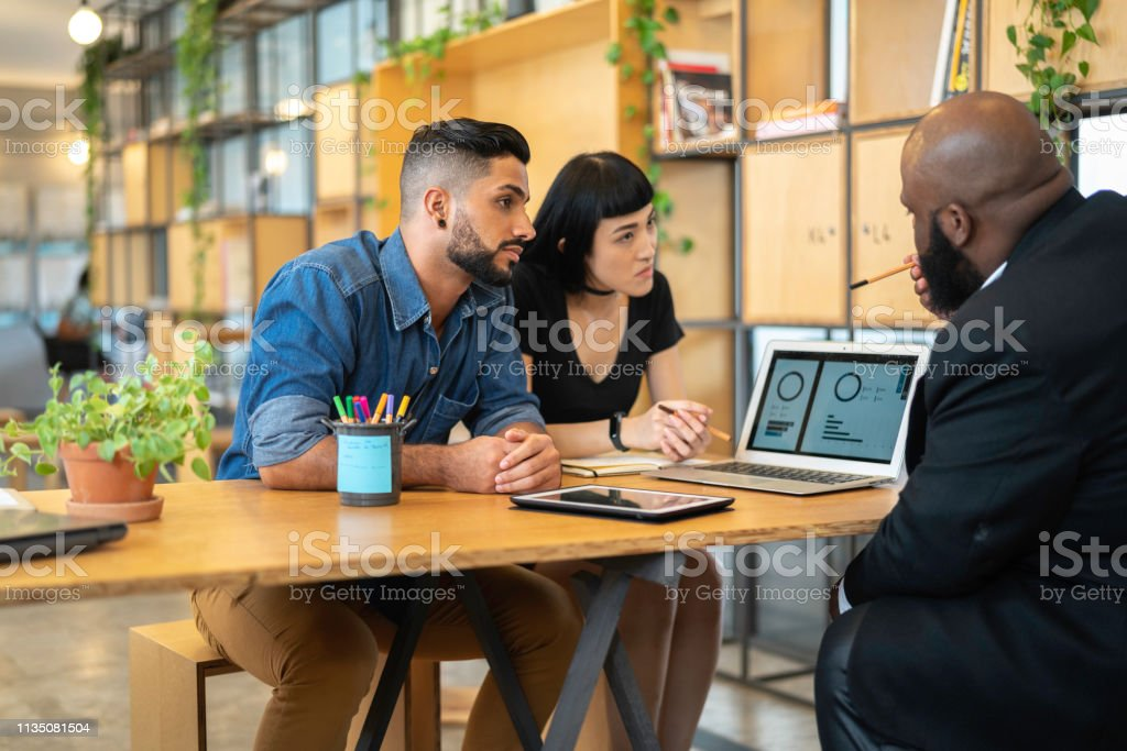 Agent talking to a couple in the office Consultant giving some advice for customer at business meeting A Helping Hand Stock Photo