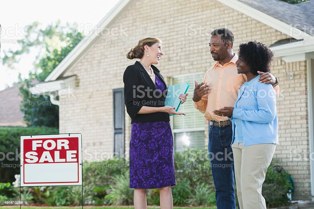 Agent talking with couple in front of house for sale stock photo