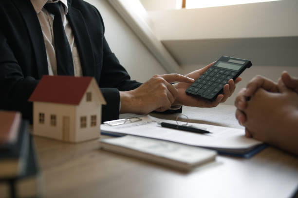 Agents are calculating the loan payment rate or the amount of insurance premiums for customers coming to contact the purchase of a new home at the office. stock photo