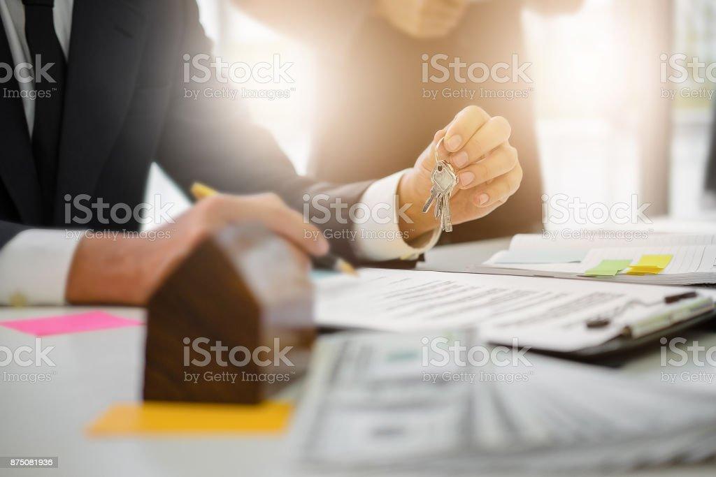 Agenten sind Hausschlüssel von Kunden- und Holding-Dollar, was uns im Büro der Agentur bank geben. Vereinbarung und Eigenschaft Konzept. – Foto