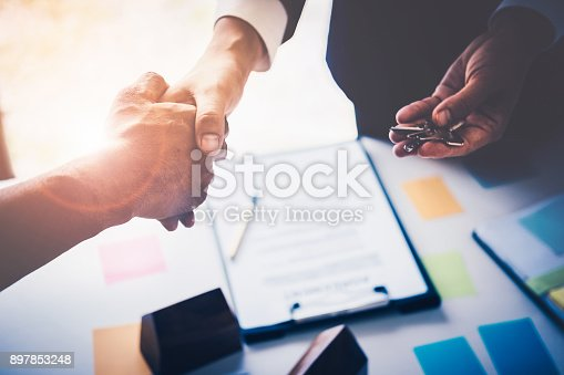 istock Agents are giving house keys of customer with handshaking after good deal at agency office. Real Estate and Agreement concept. 897853248