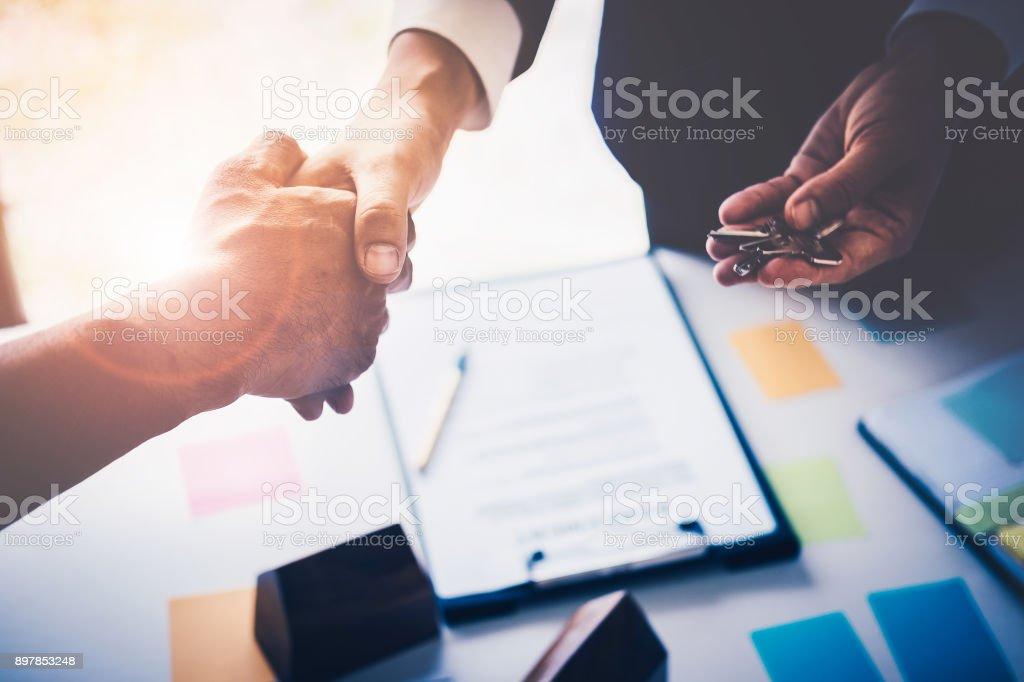 Agents are giving house keys of customer with handshaking after good deal at agency office. Real Estate and Agreement concept. stock photo