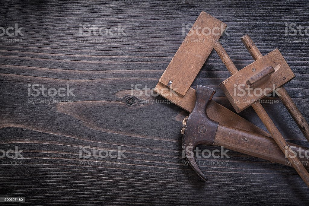 Age-old claw hammer square ruler carpenter gauge on wood stock photo