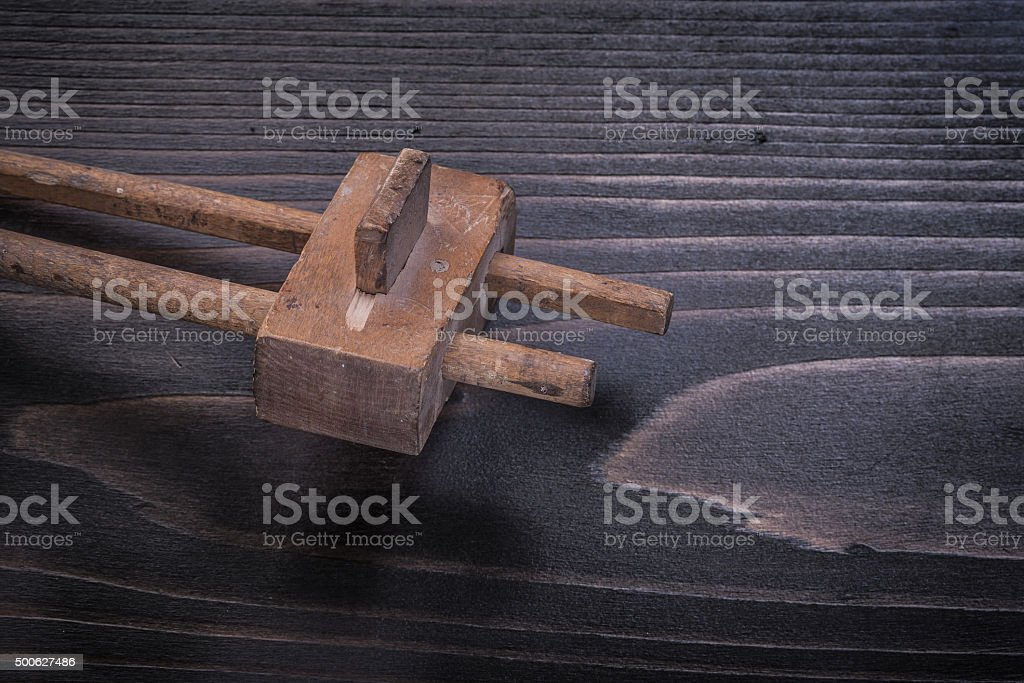 Age-old marking gauge on wood board construction concept stock photo