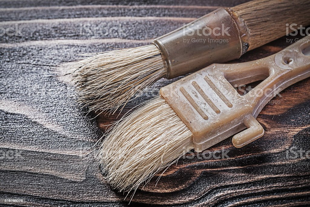 Age-old paint brushes on wooden board construction concept stock photo