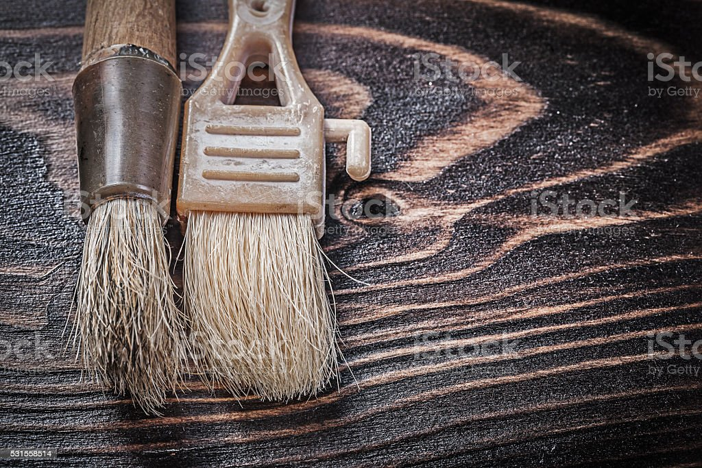 Age-old paintbrushes on wooden board horizontal version construc stock photo