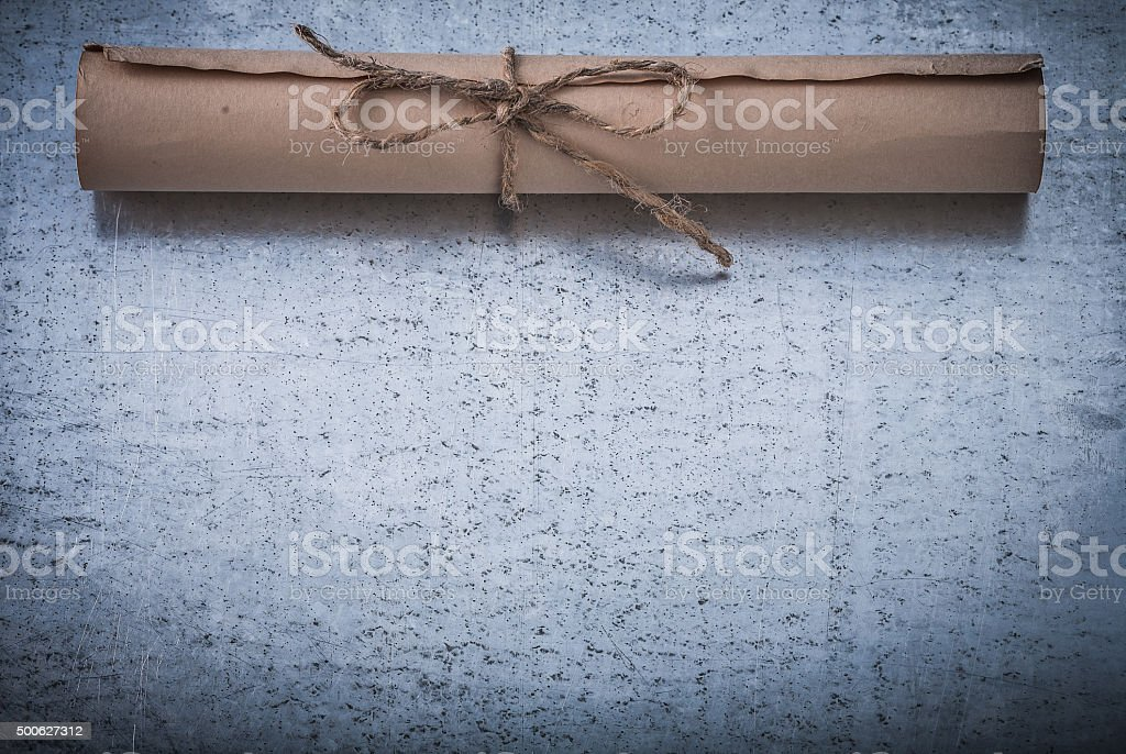 Age-old rolled corded paper on scratched metallic surface stock photo