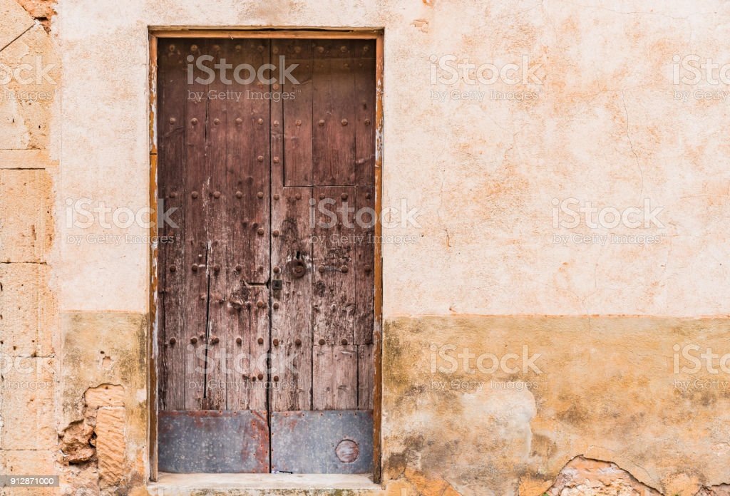 Age-old wooden front door and damaged wall background stock photo