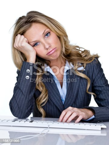 Aggravated businesswoman sitting at a desk with a computer keyboard, frowning and isolated on white background