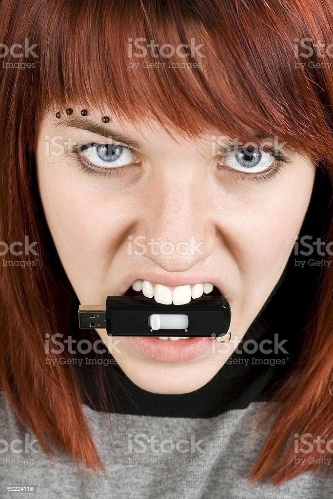 Aggresive girl biting memory stick royalty-free stock photo