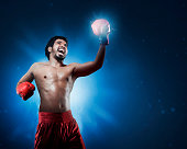 istock Aggressive asian man boxer with gloves training throwing punch 621924984