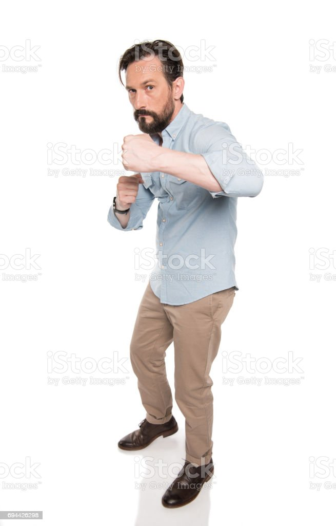Aggressive bearded man standing in boxing pose and looking at camera stock photo