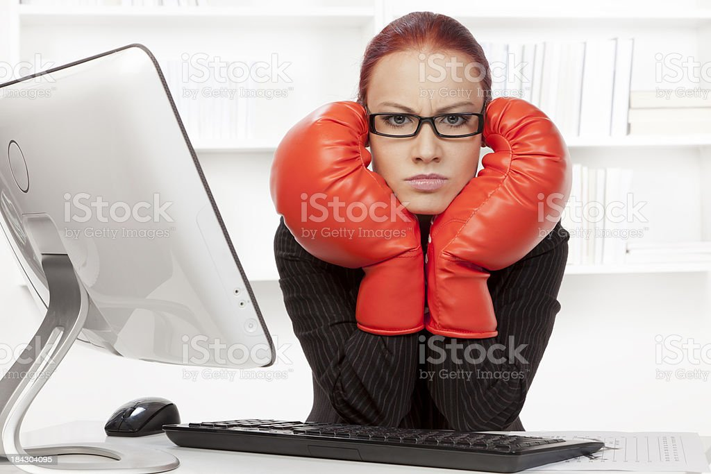 Aggressive businesswoman with boxing gloves in her office royalty-free stock photo