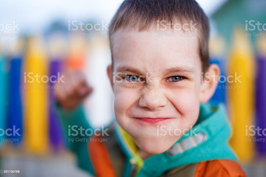 aggressive child raised his fist to strike stock photo