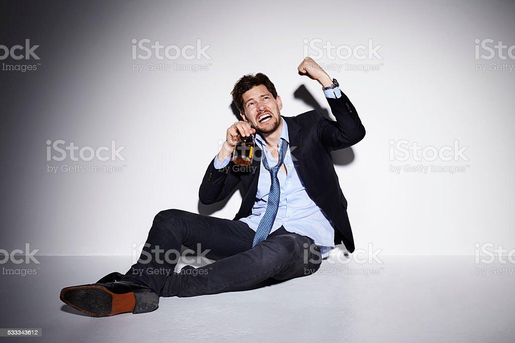 Aggressive drunk businessman shaking fist in studio stock photo
