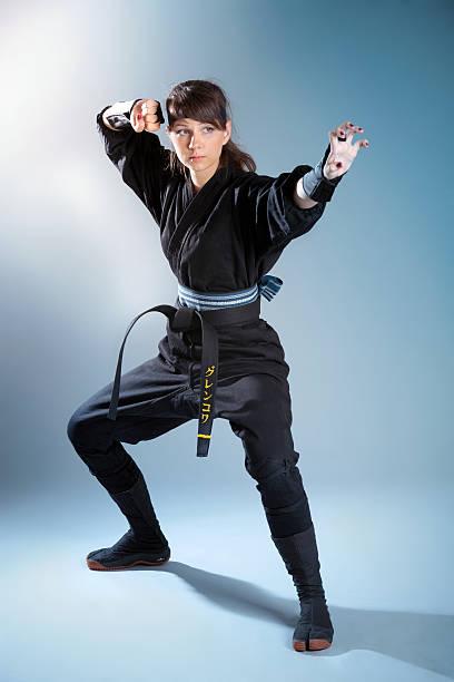 marcha mujer de pie en la lucha postura del guerrero - ninja fotografías e imágenes de stock
