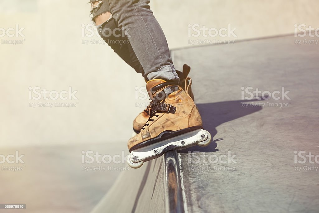 Aggressive inline rollerblader grinding on ramp in skatepark stock photo