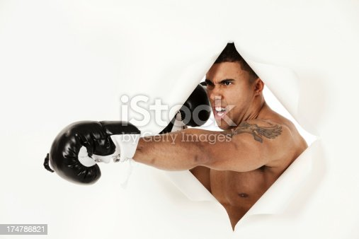 160558362 istock photo Aggressive male boxer emerging from a hole of paper 174786821
