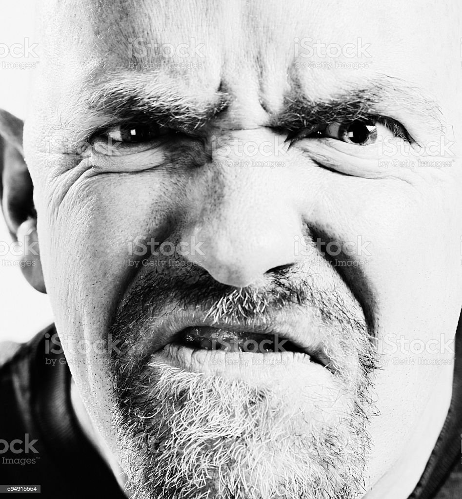 Aggressive man grimacing threateningly in close up stock photo