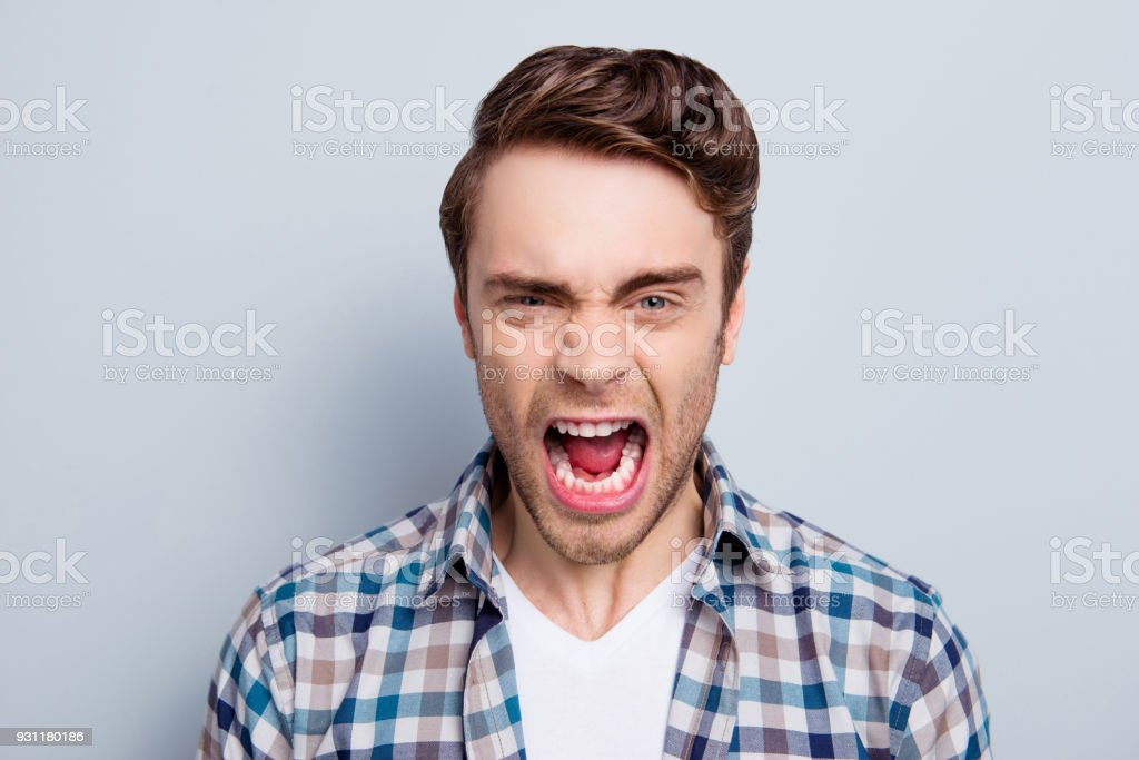 Aggressive Man In Checkered Shirt With Wide Open Mouth Is Out Of