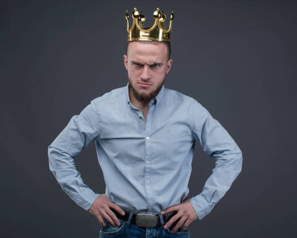 aggressive man in the gold crown with arms akimbo is staying and watchig into the camera - principe persona nobile foto e immagini stock