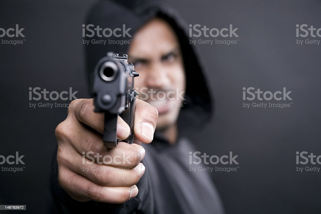Aggressive man with a gun and hoodie stock photo