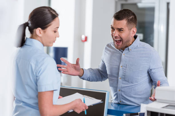 Aggressive man yelling at nurse in clinic Aggressive man yelling at nurse in clinic agitation stock pictures, royalty-free photos & images