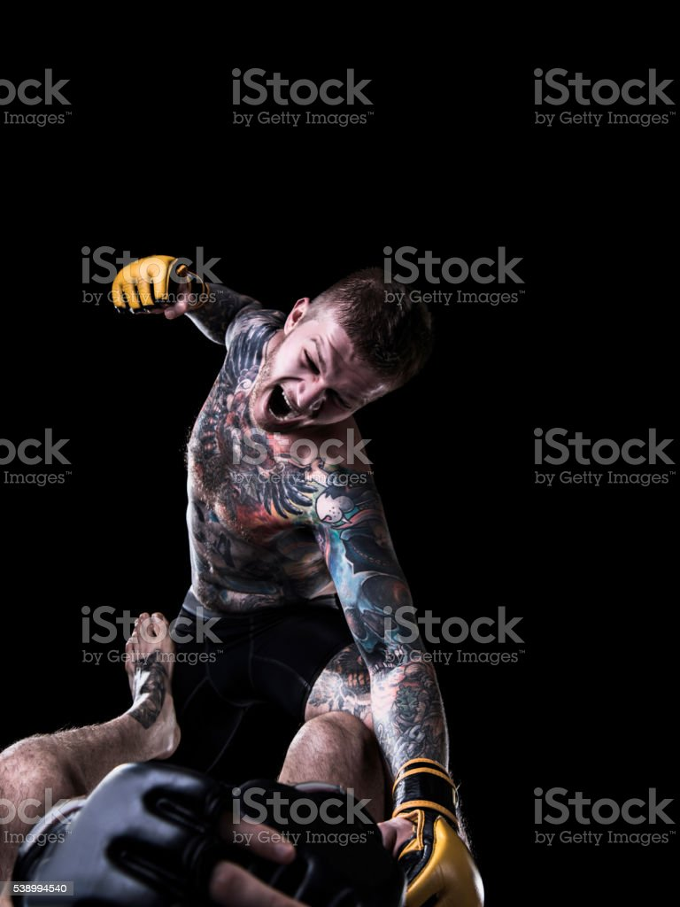 Aggressive MMA fighter punching opponent on the ground stock photo