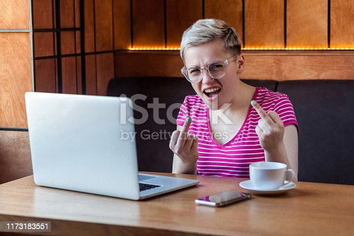 Aggressive unhappy young girl freelancer with blonde short hair, in pink t-shirt and eyeglasses is sitting in cafe and having bad mood are showing fuck sing with finger, looking at camera. indoor