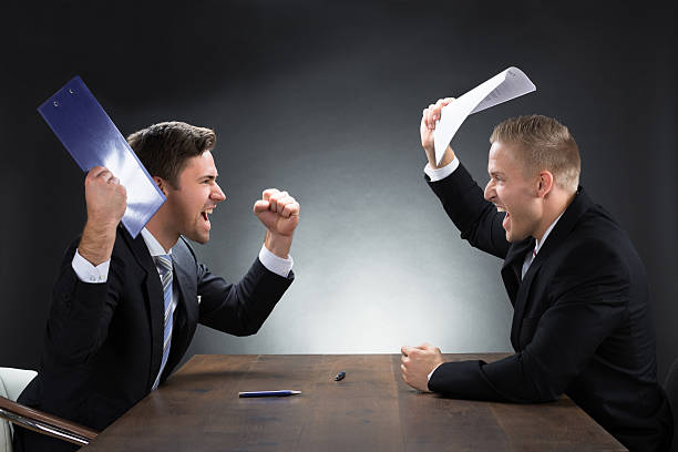 Aggressive Young Businessmen Arguing At Desk stock photo