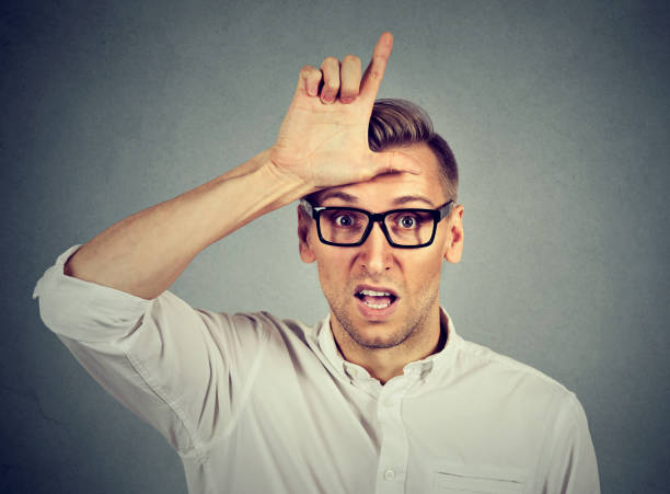 Aggressive young man in glasses showing loser sign gesture on forehead Aggressive young man in glasses showing loser sign gesture on forehead, looking at you with disgust isolated on gray background. Negative human emotions, facial expressions, feeling antagonize stock pictures, royalty-free photos & images