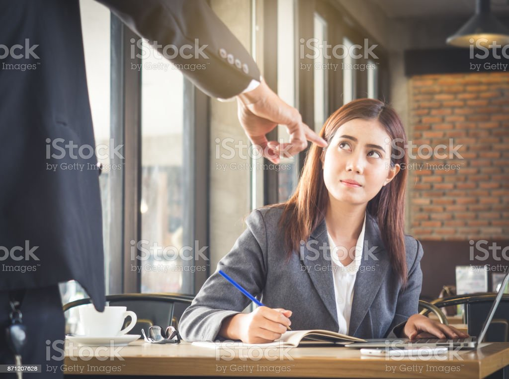 Aggressive/angry boss complaining asian business woman(casual uniform) in cafe office stock photo