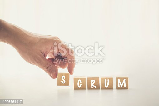 istock Agile and Scrum in Software Development concepts, Hand pick wooden cube and place with text to fill the word SCRUM. Brochure design template, card, banner with copy space for label text. 1226761417