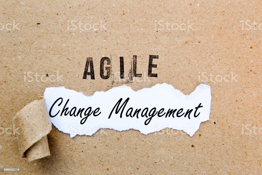Agile Change Management - printed text underneath torn brown paper with Agile printed in ink stock photo